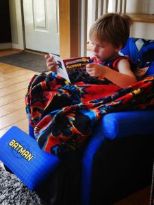 """Reading"" in his Batman chair."